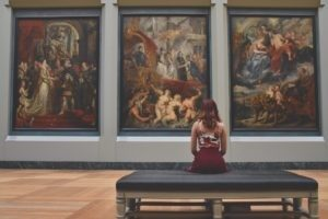 A girl looking at some pictures at the museum - it is only a piece of culture you'll see when moving to Toronto.