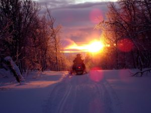 A man driving a snowmobile in a sunset