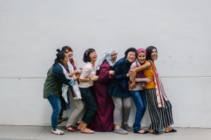 Women belonging to different cultures holding each other in a line - multiculturalism is a part of Canadian culture