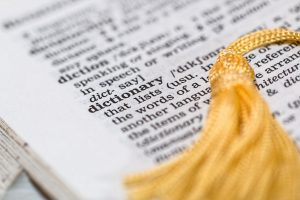 An open dictionarywith the word dictionary and yellow tassel