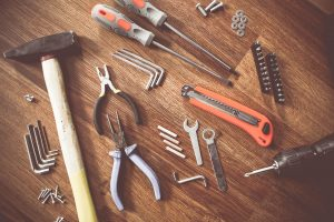 A hammer, screws, wrenches and other tools.