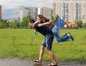 A man carrying a woman over a puddle.