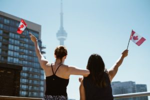 Two girls holding Canada flags afterdeciding on the things to visit after moving to Toronto.