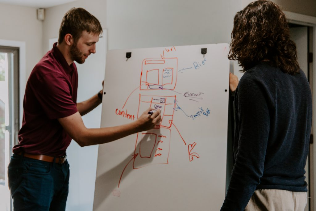 A man drawing and explaining on a board