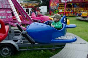 a boy in an amusement park as one of the solutions to help your kids adapt to a new country.