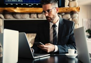 A man in a suit is sitting in front of a laptop holding  mobile phone.
