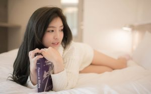 A girl holding a book in her room.