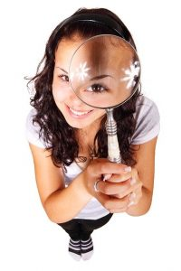 A woman with a magnifying glass understands the importance of reading a moving contract.