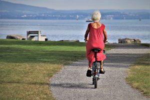 Older woman is biking.